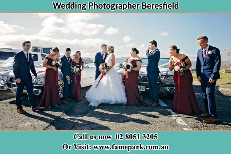 Photo of the Bride and the Groom kissing while teasing by their brides maid and groom men Beresfield NSW 2322