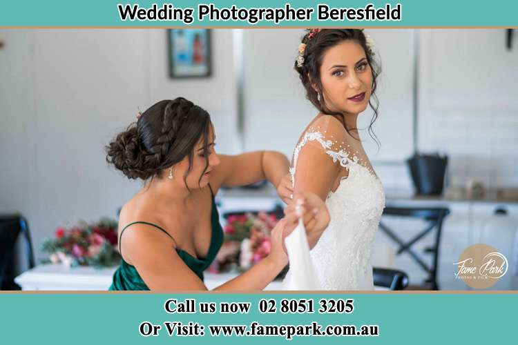 The Bride is being helped by bridesmaid trying to put her bridal gown Beresfield