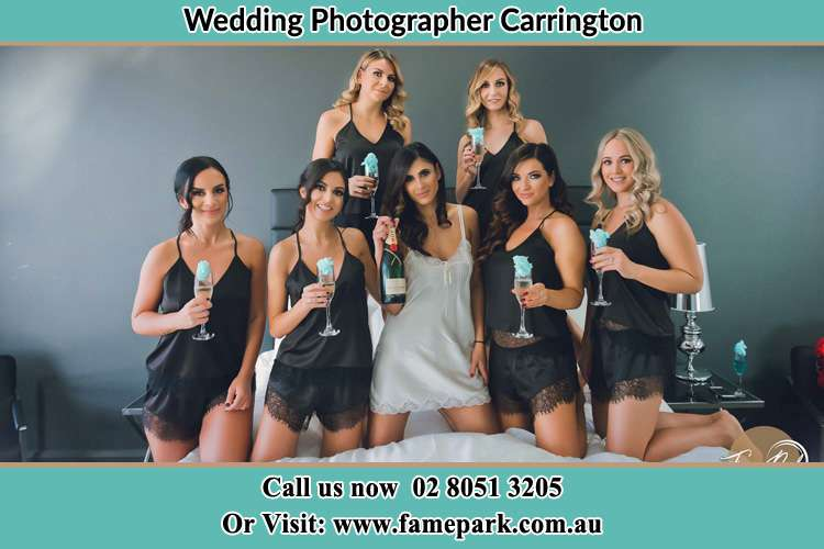 The bride holding a bottle of wine poses with the girls in front of camera Carrington