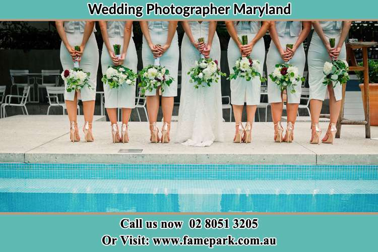 Photo of the Bride and her bridesmaids holding flower posing behind the camera Maryland NSW 2287