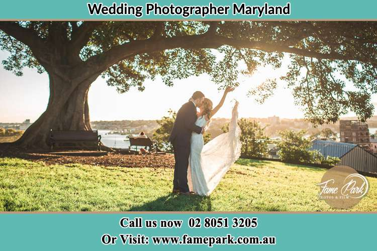 Photo of the new couple kissing under a big tree Maryland