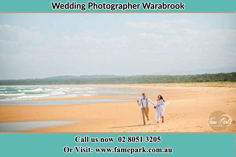 Photo of the Groom and the Bride walking at the sea front Warabrook NSW 2304