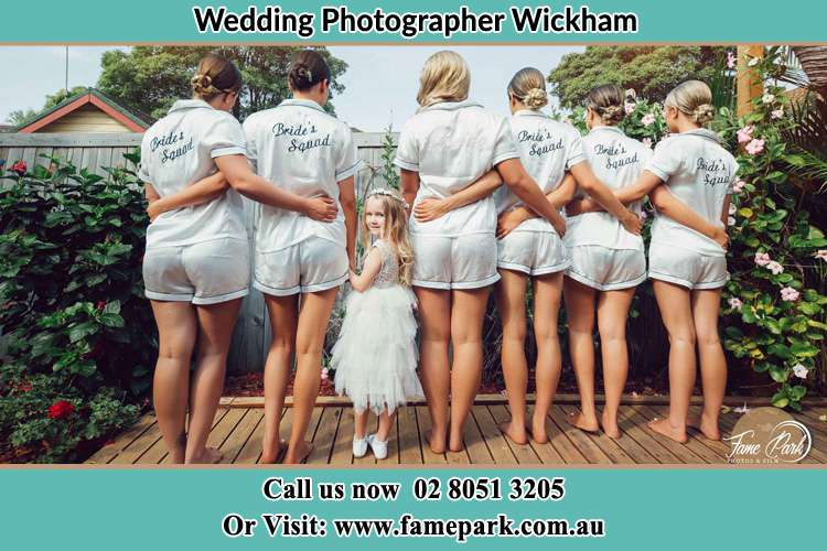 Behind photo of the Bride together with her bridesmaid and flower girl looking back Wickham NSW 2293