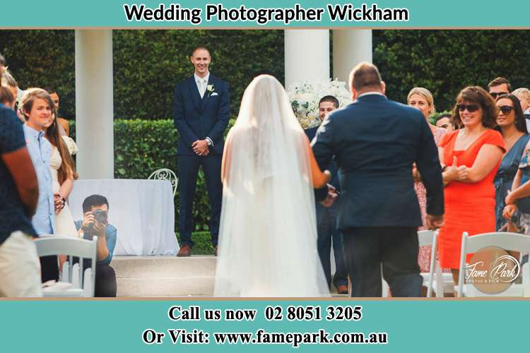 Photo of the Bride accompany by her father going to the waiting Groom Wickham NSW 2293