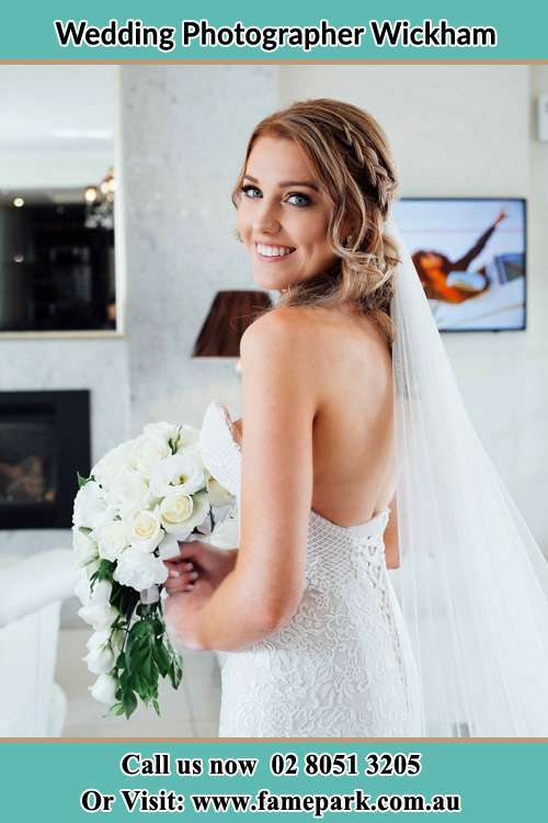 The Bride holding a bouquet of flowers smiles in front of the camera Wickham